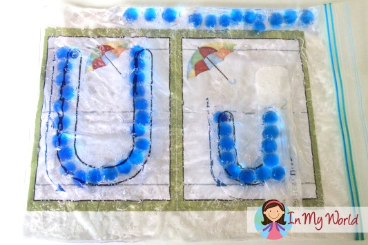 Learning to write the letter U with a hair gel and beads sensory bag